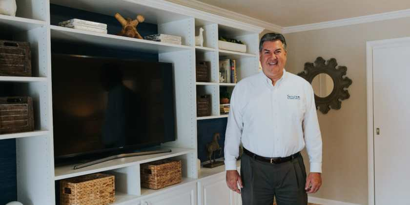 Photo of Tim Meehan in front of his built-in entertainment center by Closets by Design