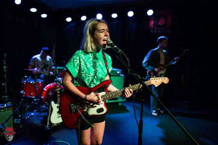 Snail Mail singing into a microphone.