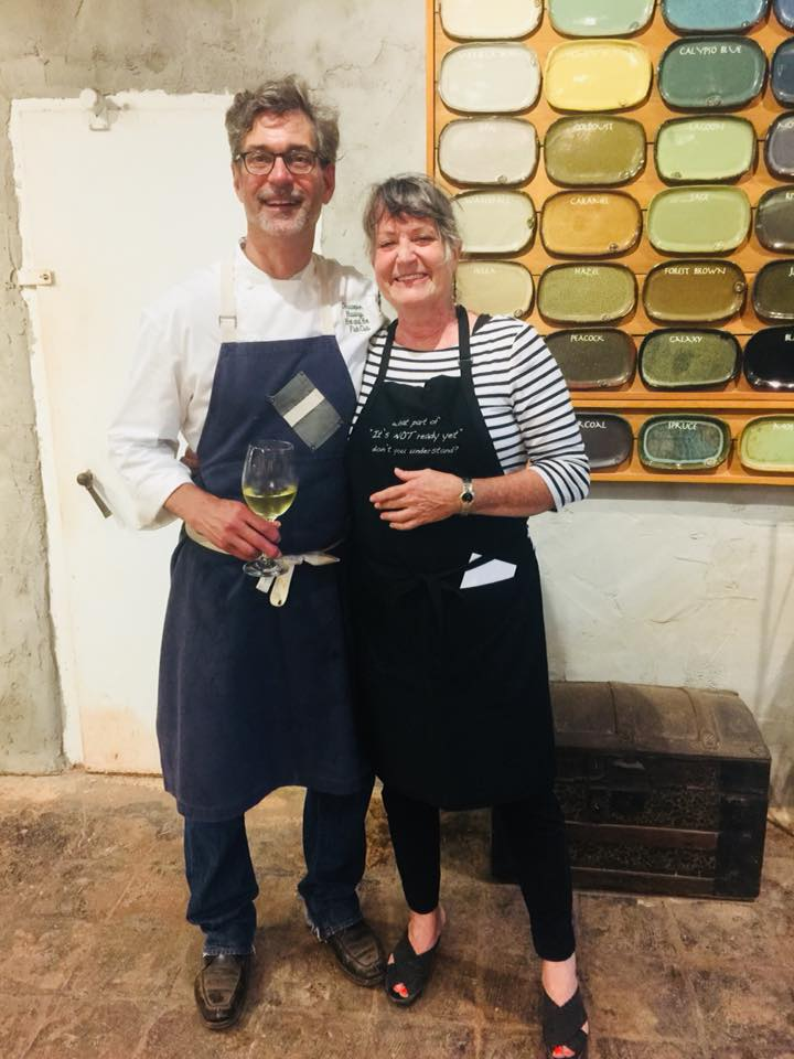 Chris Hastings and Tena Payne in front of a wall of pottery