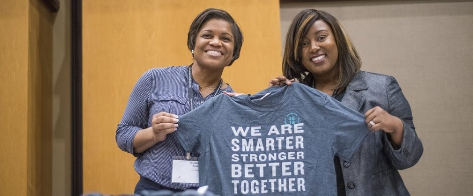 Two women at a Momentum Conference holding a shirt that says We are smarter stronger better together