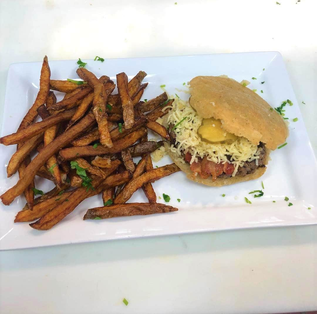 An arepa burger served with fries