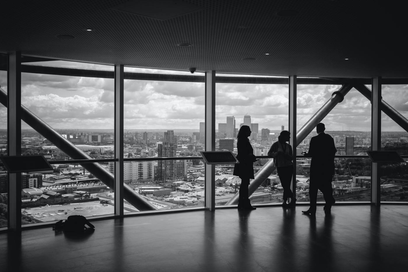 People beside a window in a business setting.