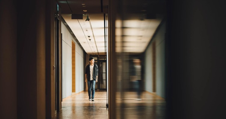 man walking towards opened door