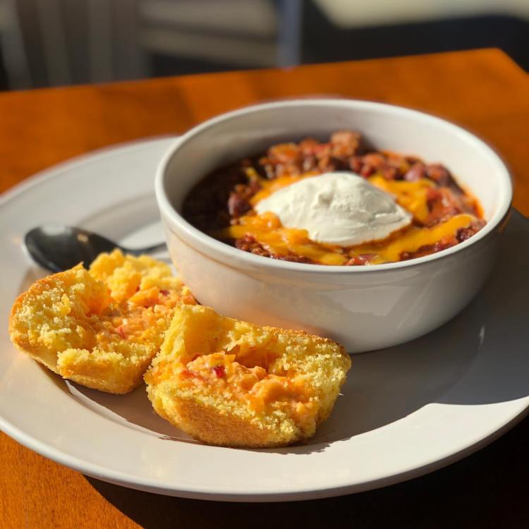 A bowl of chili with cornbread on the side