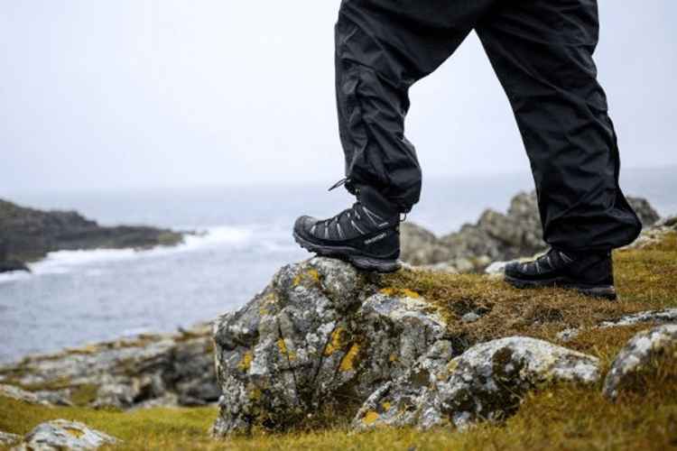 Picture of person with hiking shoes on a bluff over the ocean.