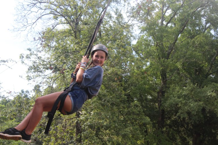 camper on a zip line at YMCA Camp Cosby