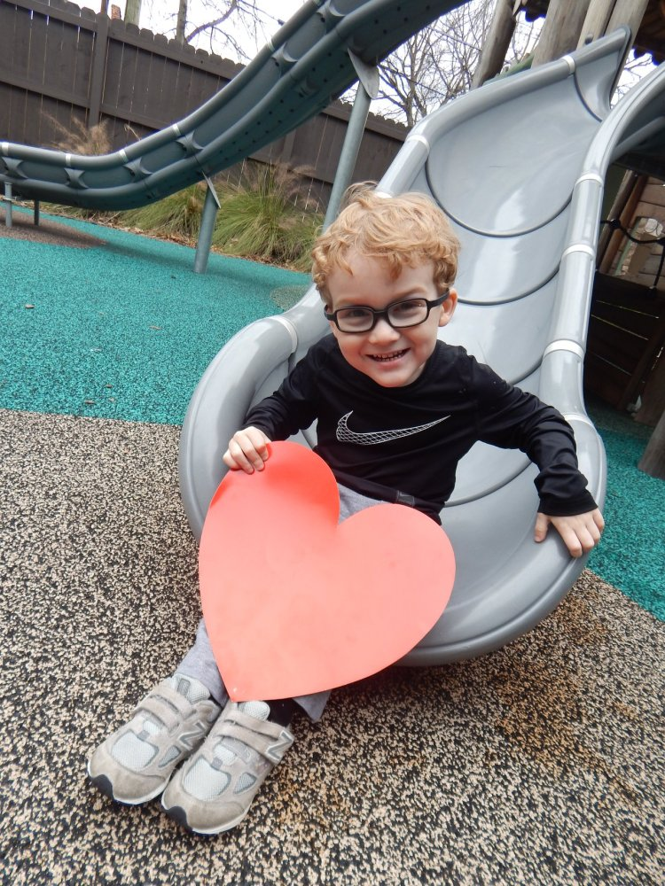 child smiling holding a paper heart, send a valentine to the Ronald McDonald House in Birmingham