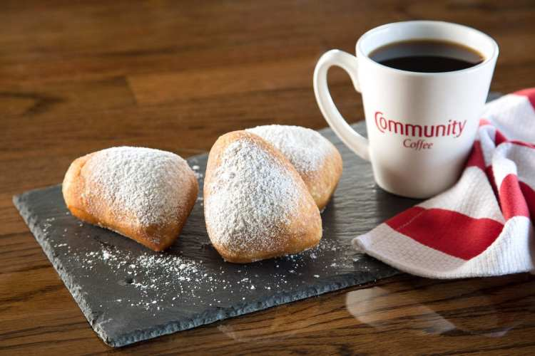 Beignets next to cup of coffee - places to get breakfast in Chelsea