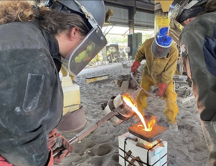 metal workers pouring red hot iron