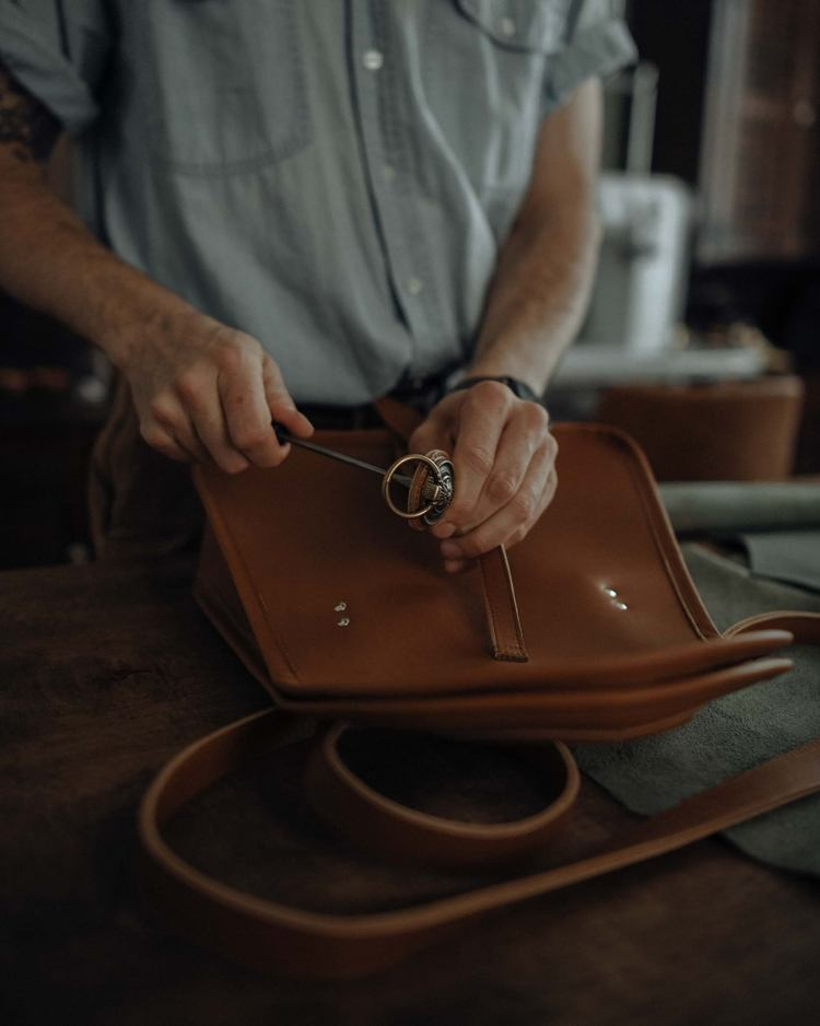 man working on leather purse