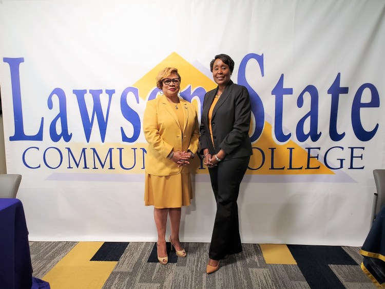 Two women standing in front of white banner that says Lawson State Community College