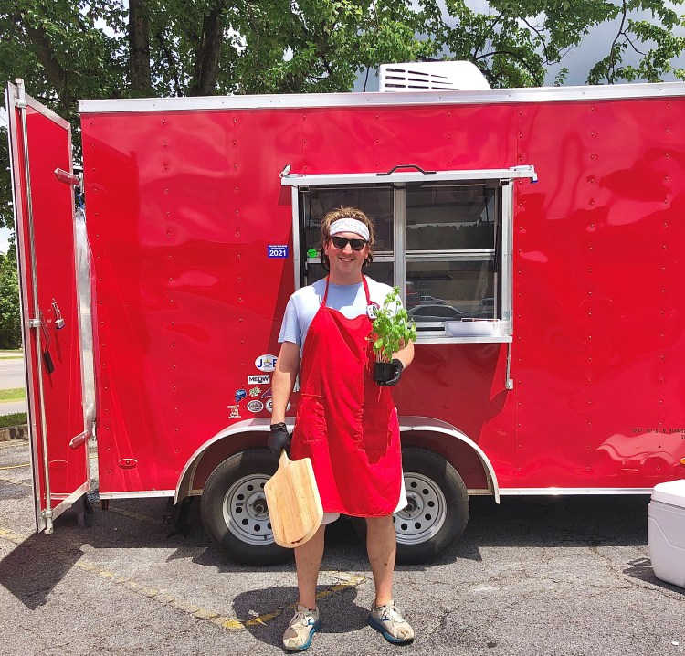 Man in white shirt and shorts with red apron holding pizza peel and herbs in front of red trailer