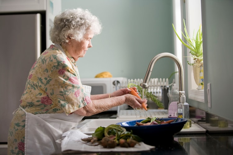elderly woman washing a carrot