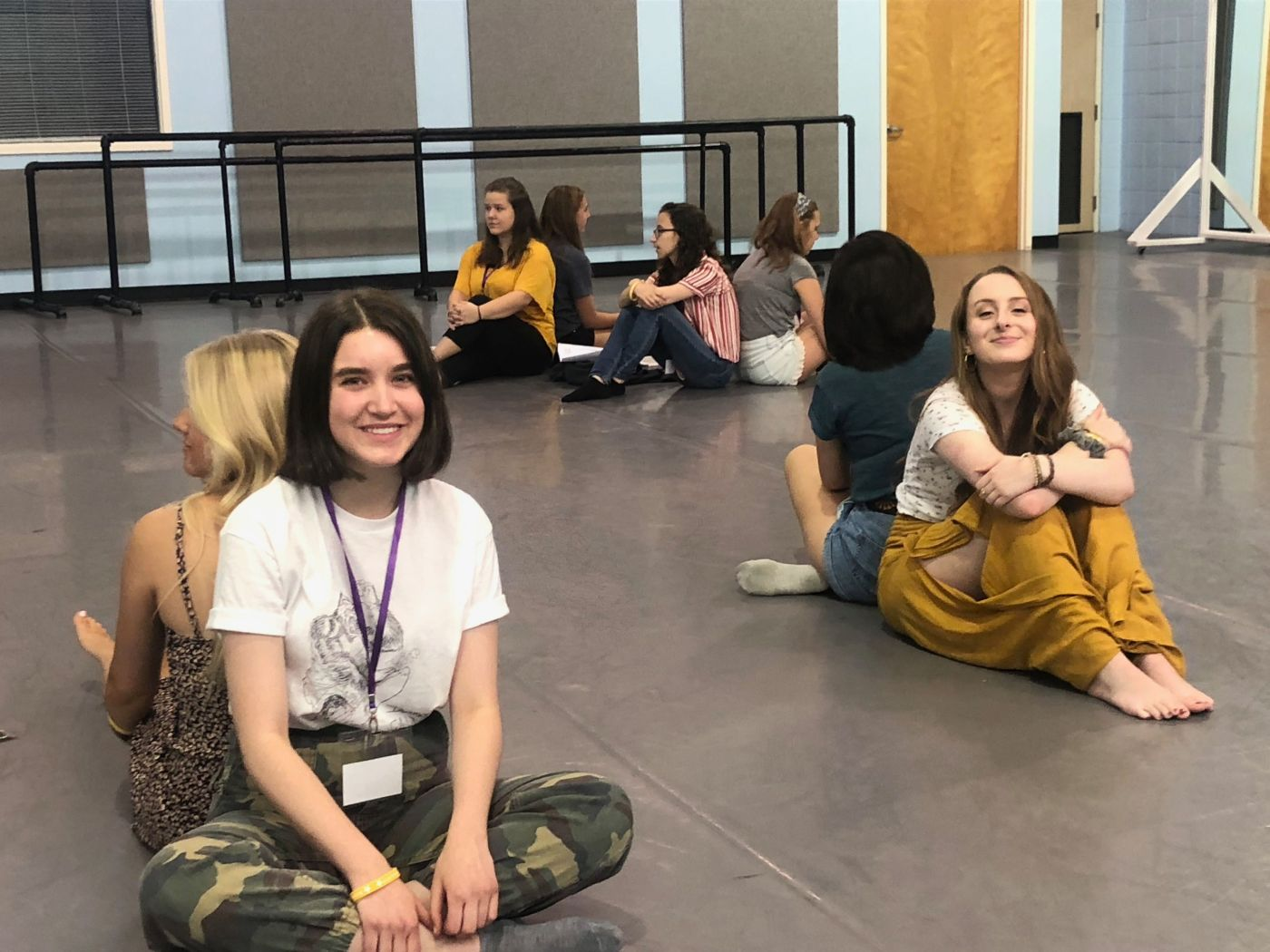 Two  instructors sitting on the floor smiling