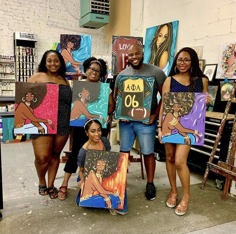 group of people holding paintings from the art class