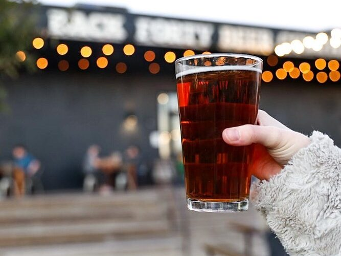 pint of brown ale held in a person's hand