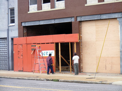 Workers removing signs announcing the pending arrival of New Vulcan Ale House. acnatta/Flickr