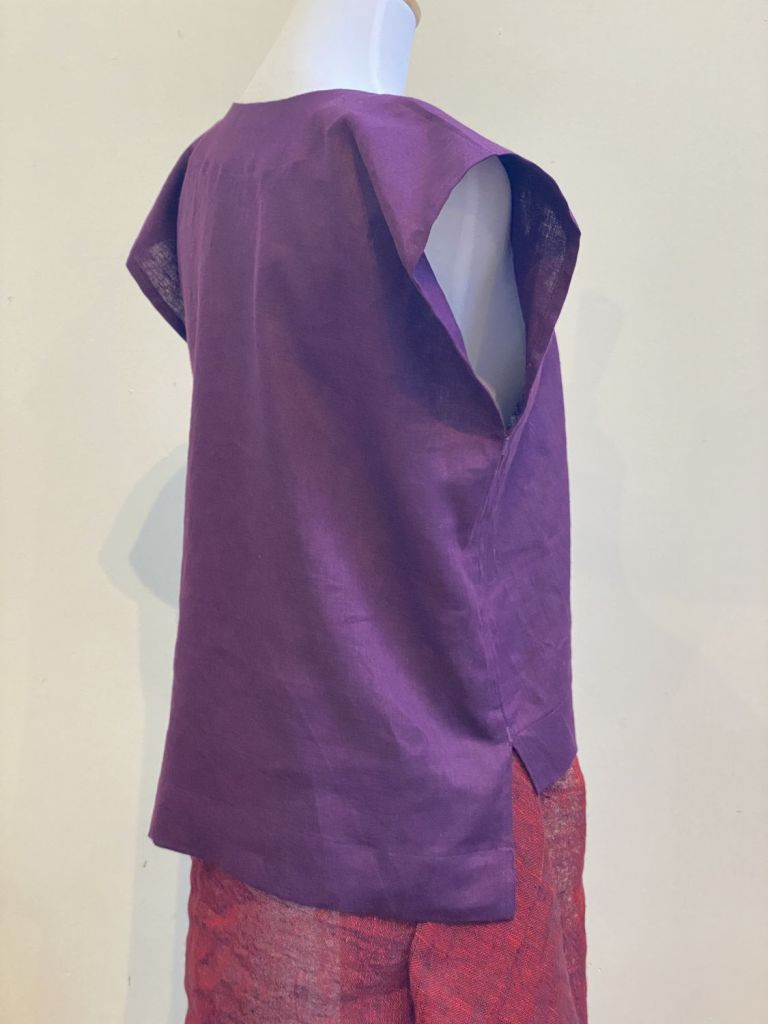 Yarrow top in bright purple linen, displayed on a mannequin and photographed from behind and to the right. This displays the cap sleeve and the side-slit and high-low hem. The Yarrow top is a sustainable, ethically made garment.