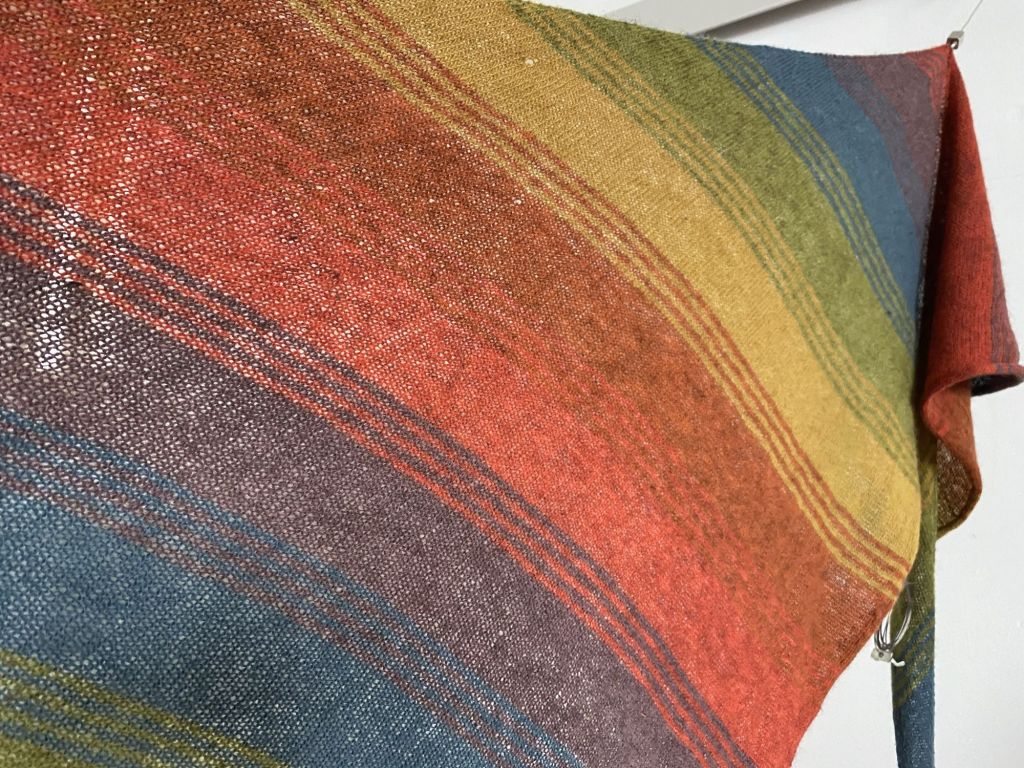 rainbow striped scarf spread out to show the progression of colours