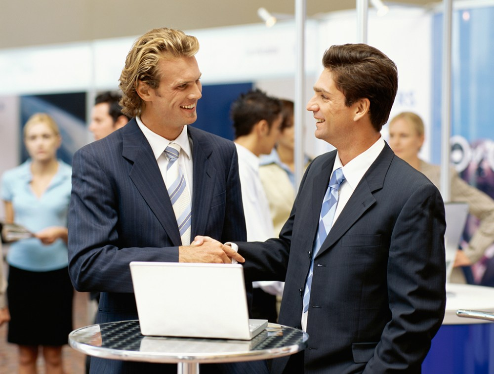 two businessmen shaking hands at an exhibition