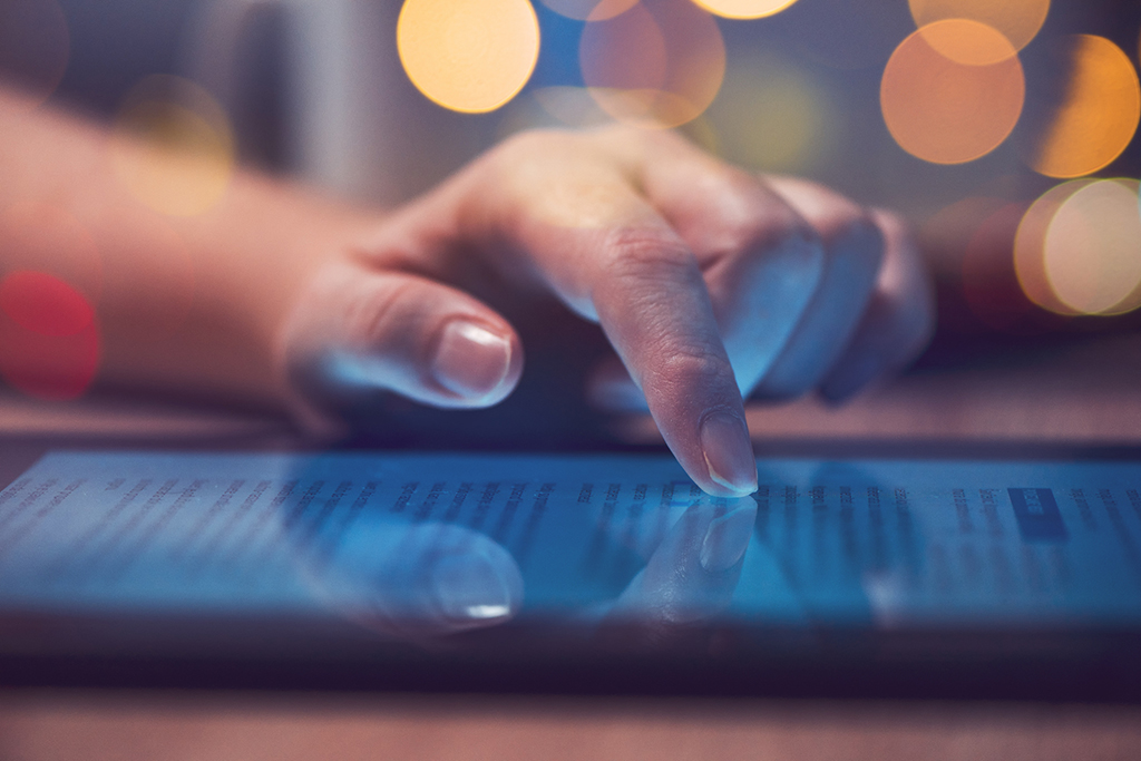 Woman reading online news on digital tablet