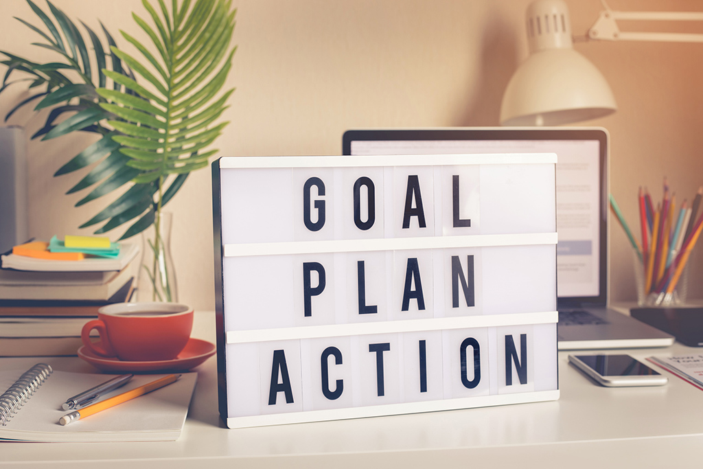 Goal,plan,action text on light box on desk table in home office.Business motivation or inspiration.