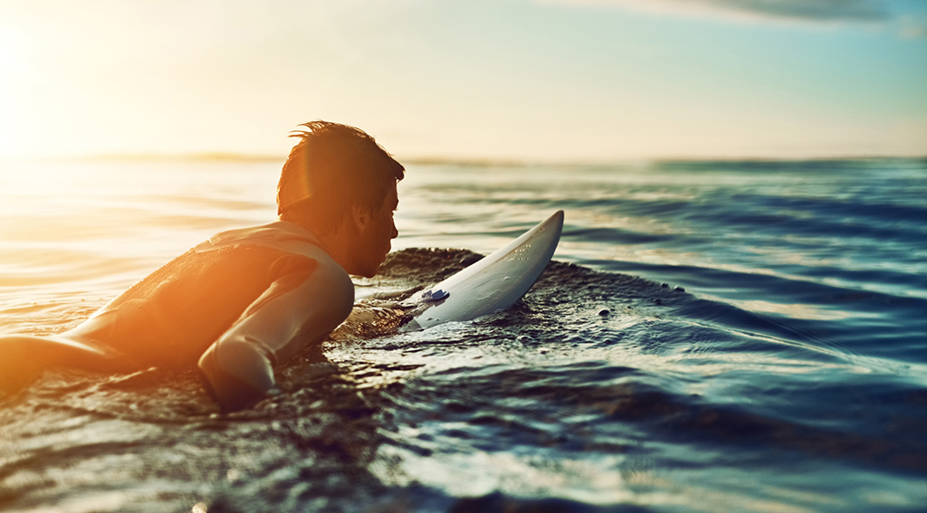 Shot of a young boy out surfing