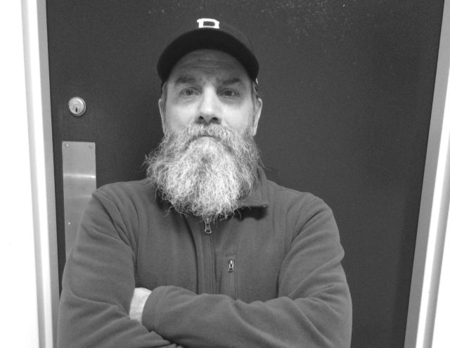 Michael Coccetti, a Burlington High School custodian, poses in the hallway. Coccitti is an avid baseball fan and hands out cards to community members.