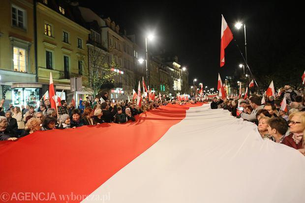 Wieczorem na Krakowskie Przedmieście w Warszawie kolejny raz wczoraj przyszły setki osób, wiele trzymało biało-czerwone flagi, inni rozciągnęli kilkunastometrową flagę