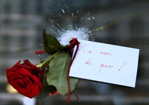 Róża w przestrzelonej szybie restauracji w Paryżu, gdzie wczoraj zginęło kilkanaście osób. Na kartce napisano