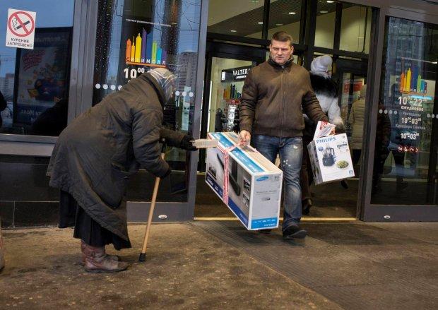 Kiedy wartość rubla drastycznie spadła, ludzie rzucili się do wykupywania importowanych towarów. Na zdjęciu: klient wychodzi z hipermarketu w Petersburgu, grudzień 2014