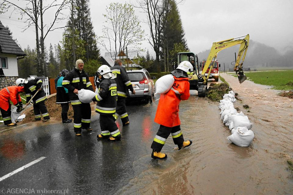 Podhale , Kościelisko . Strażacy z OSP Witów pogłębiają rów melioracyjny i stawiają zaporę z worków z piaskiem aby woda z pol nie zalała drogi prowadzącej do Witowa