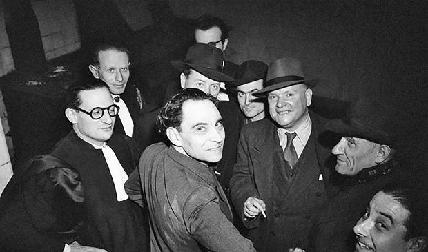 Marcel Petiot (1897-1946) uważany jest przez Francuzów za jednego z najbardziej odrażających seryjnych zabójców, którzy działali nad Sekwaną. Liczba zamordowanych przez niego osób nie została dokładnie ustalona. Wiadomo natomiast, że problemy psychiatryczne miał już w młodości, po odniesieniu ciężkiej rany podczas I wojny światowej. Mimo to dostał zezwolenie na praktykę lekarską, którego nigdy mu nie odebrano mimo licznych udowodnionych mu przestępstw pospolitych i medycznych. Pierwszą zbrodnię popełnił najpewniej w latach 20. Na zdjęciu zrobionym wiosną 1946 r.: Petiot w otoczeniu prawników i reporterów przed wejściem na salę rozpraw.