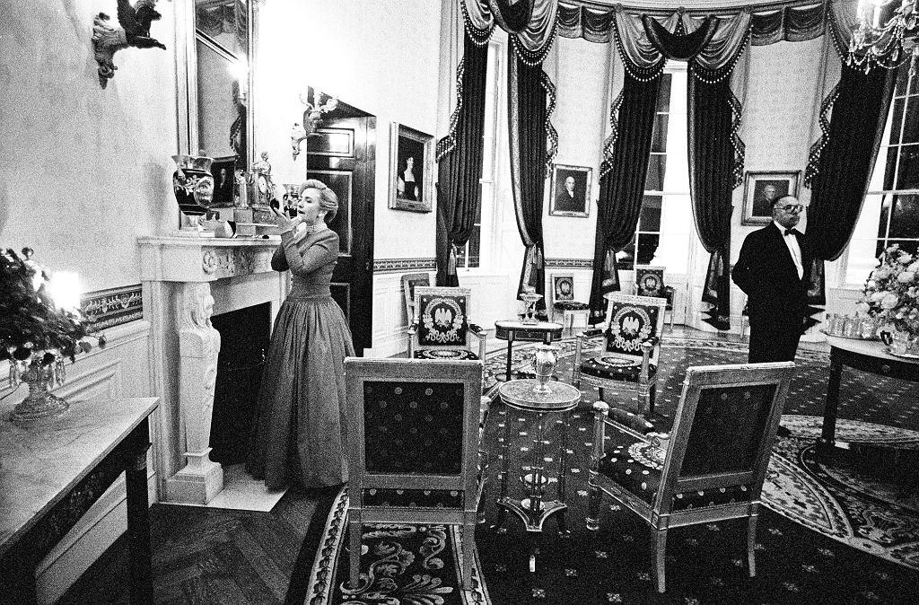 Hillary Clinton poprawia makijaż w Niebieskim Pokoju przed kolacją dla krajowej rady gubernatorów, z tyłu stoi długoletni kamerdyner James Jeffries. Clintonowie, podobnie jak Kennedy i Johnsonowie, uwielbiali przyjęcia, co odbiło się na personelu. Jeffries pamięta, jak poradził zmęczonemu Billowi Clintonowi: