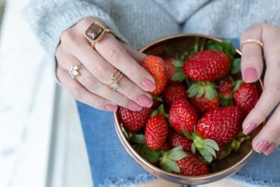 Mãos de mulher com vários anéis segurando um bowl de cobre cheio de morangos