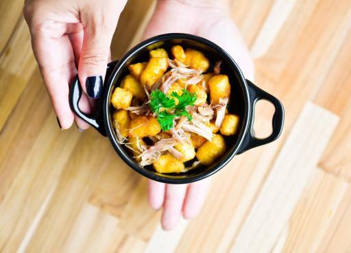 Mini cocote preta com nhoque frito e pato desfiado e uma folha de salsinha. Sendo segurado com uma mão e a outra dando suporte em baixo.