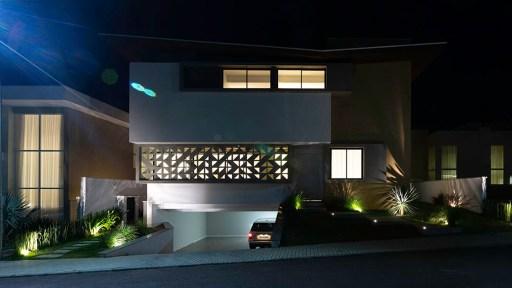 Fotografia de arquitetura noturna: Casa com telhado invertido, volumes bem marcados e cobogó na fachada, fotografada à noite. Isso evidencia os cobogós da fachada, por onde vaza a luz do interior da casa.