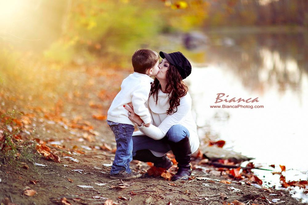 Mother kissing son at waters edge