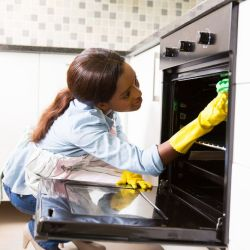 bigstock-african-woman-cleaning-stove-i-747859781