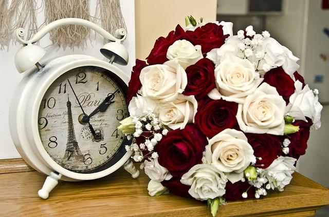テーブルの上に時計とバラ