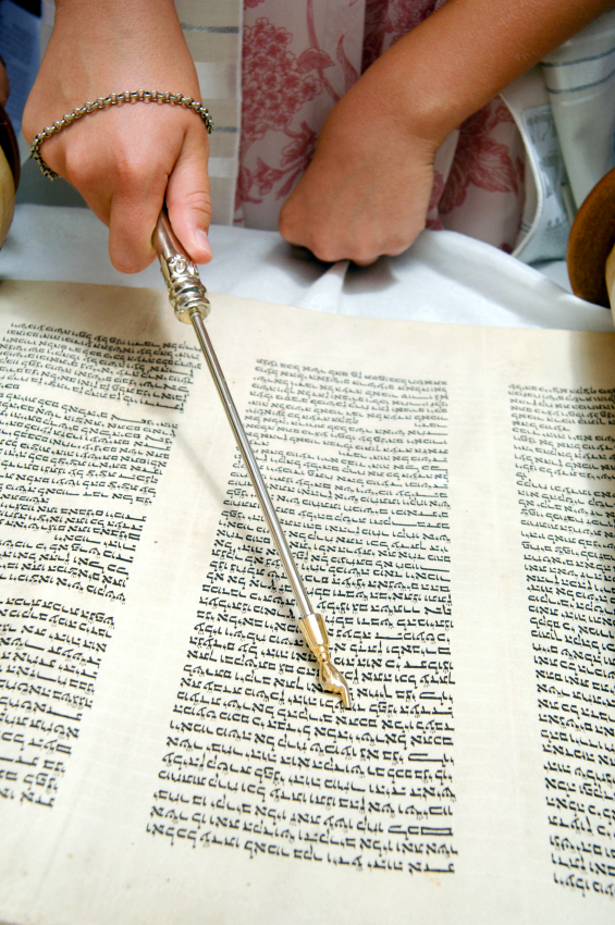 Reading the Torah scroll, using a yad (Torah pointer) to follow along in order to both protect the parchment and the handwritten text, and to show reverence for the Word of God.