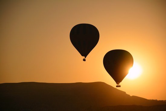 Two Hot Air Balloons Floating Gently At Sunrise Above Rose Valle