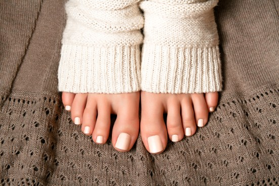 Beautiful beige pedicure. Feet in soft knitted socks on a brown plaid lace