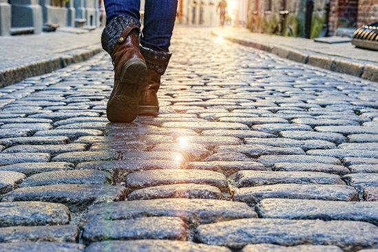Legs of a woman walking along cobbled streets of European cities.