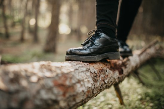 Feet in black shoes walking and balancing on a fallen tree trunk
