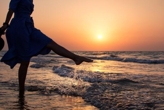 Girl Walking Towards Water At Sunset