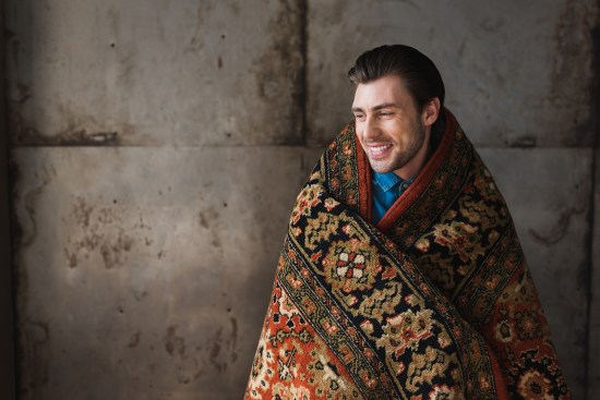 Happy Young Man Covered In Rug In Front Of Concrete Wall