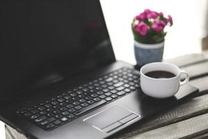 Kaffekopp bredvid en bärbar dator med en liten blomma bredvid.