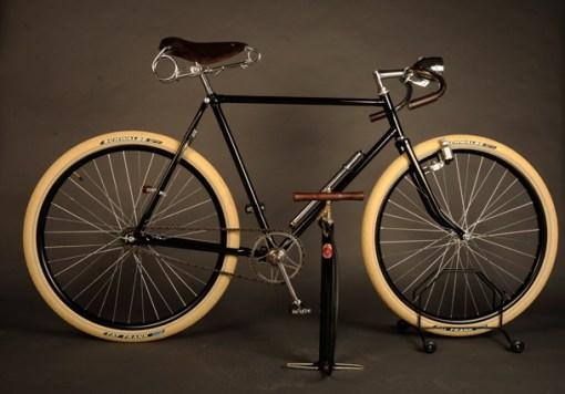 Bomba pie con agarre de madera con dos estribos plegables en exposición con bicicleta