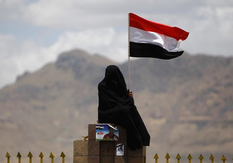 A woman holds the national flag during a parade at a celebration by anti-government protesters commemorating the anniversary of Yemen's reunification, in Sanaa May 22, 2011. Yemen's President Ali Abdullah Saleh was due to sign a pact on Sunday to become the third Arab leader ousted this year by protests, under stronger diplomatic pressure this time after twice backing out at the last minute. REUTERS/Ammar Awad (YEMEN - Tags: POLITICS CIVIL UNREST ANNIVERSARY IMAGES OF THE DAY) - RTR2MQN6